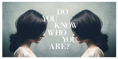 Mirror image of woman in white top standing in front of a gray wall. Photo represents one's assessment of who they are.