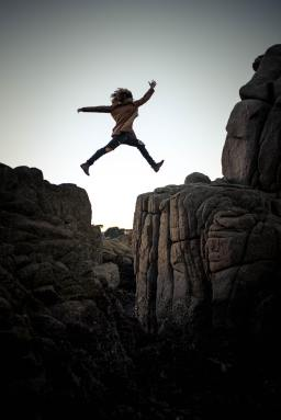 Photo of a person leaping across a canyon representing how trusting God will help you live beyond fear.