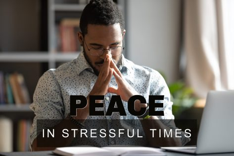 A young black man sitting at a desk with an open book and laptop in front of him. His head bowed, eyes closed and hands in the praying position. Photo represents seeking peace in stressful times.