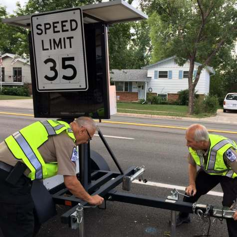 Bernie and Roger set up a speed sign to warn drivers to slow down