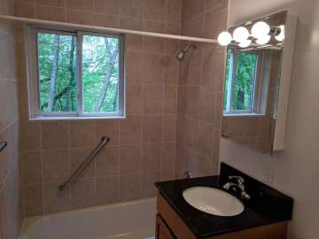 Bathroom with ceramic tile walls and window facing trees.