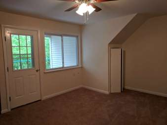 Living room looking towards from door with windows and sliding picture window next to it.