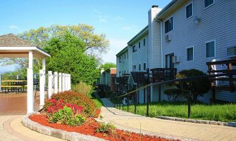 Path by gazebo with landscaped bushes, flower and mulch with apartment buildings on the right.