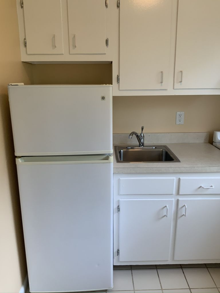 White cabinets, refrigerator and stainless steel sink.