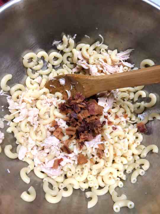 Combining the ingredients for the ranch pasta salad. ​