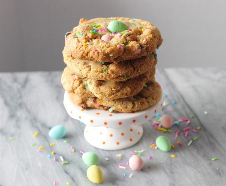 mini-egg cookies stacked on a stand with mini eggs and sprinkles in the foreground