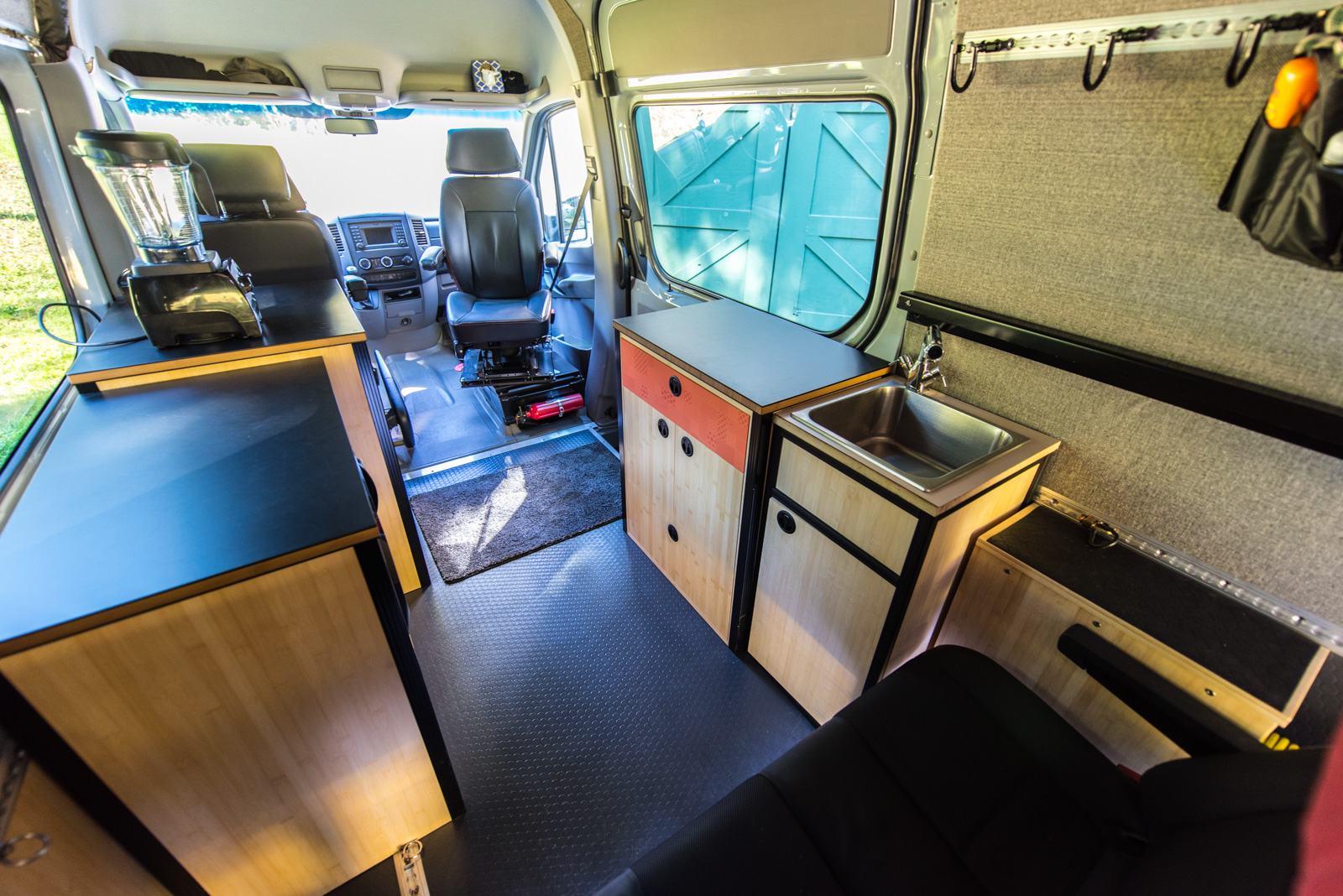 Living area of the van - bench seat moved to third passenger position to make space for cabinetry. Swivel on passenger seat