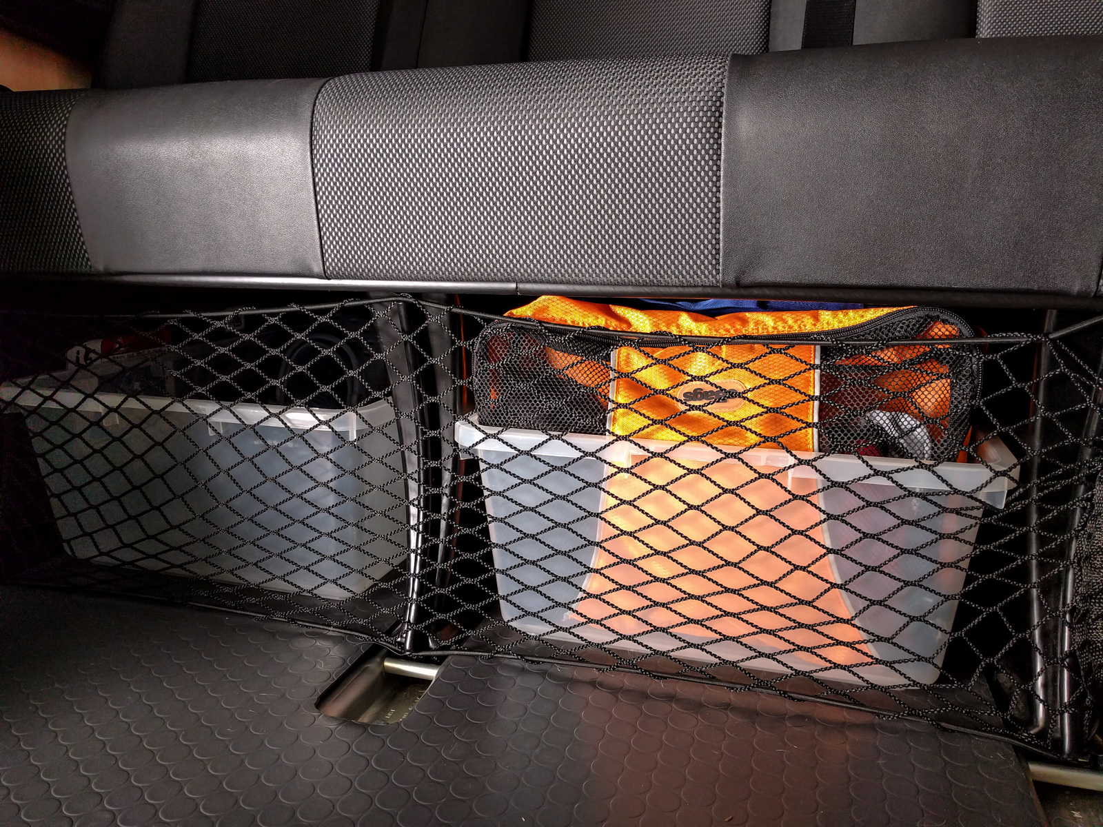 Clothes storage in packing cubes in plastic tub under bench seat