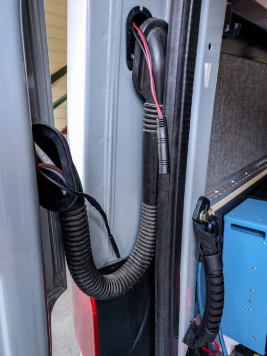 Camera cable threading through the flexible boot between the rear door and the body of the van