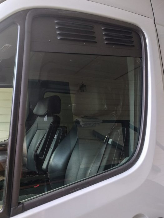 Metal vent in the top of the driver's door window area