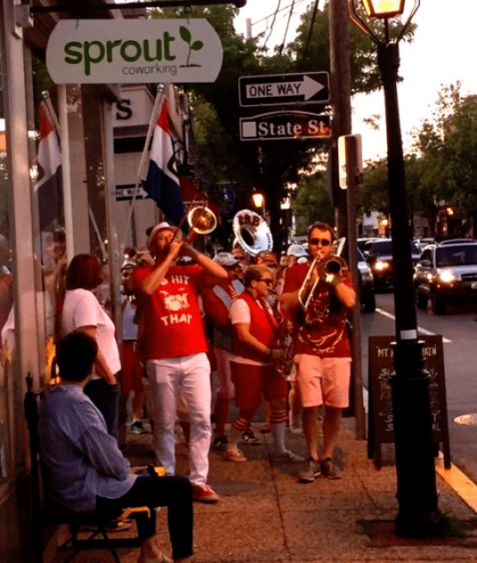 Sprout CoWorking Warren. The Extraordinary Rendition Band plays in a procession just outside on Main Street.