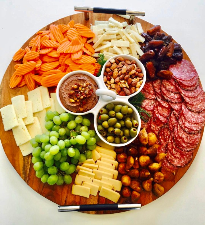 Beautiful Charcuterie Board with different fruits both fresh and dried, nuts, olives, cheeses. A board that makes your mouth start watering it looks so good. For more recipes follow www.sprouting-vitality.com #sproutingvitality #kenzinthekitch #healthyrecipes #culinaryarts  #createacharcuterieboard