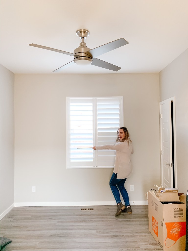 picture of a woman measuring a window in a empty room