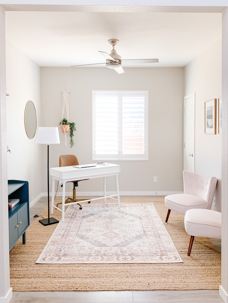 picture of an office with a rug, desk, cabinet and two chairs