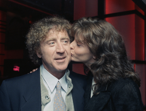 """Actor Gene Wilder, left, gets a kiss from co-star Joan Severance during a premiere benefit for their new movie """"See No Evil, Hear No Evil"""" Wednesday, May 11, 1989, New York. The benefit was held for the New York League for the Hard of Hearing. (AP Photo/Ron Frehm)"""