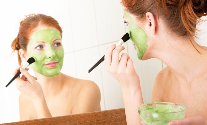 A woman putting on facial peel in her bathroom.
