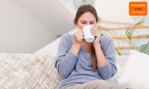 Woman drinking tea to treat sore throat.
