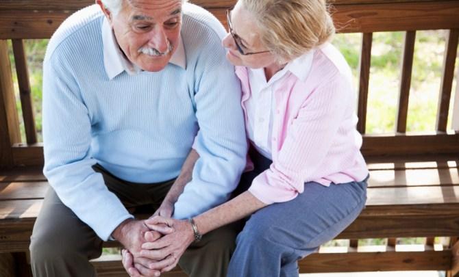 Senior woman consoling sad husband.