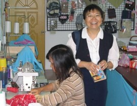 Sister Rose Chiu assists a student with a sewing project at Reed School
