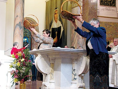 Sister Jane Marie Osterholt (left) and General Superior Sister Denise Wilkinson lift the baskets of commitment statements during the blessing.