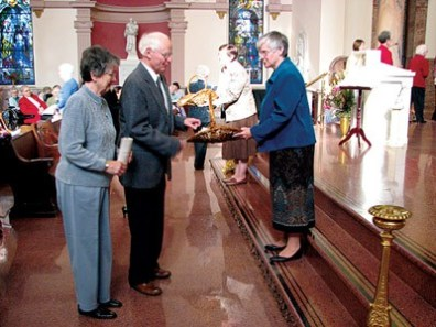 Paul Salstrom of Saint Mary-of-the-Woods Village, presents his commitment statement to General Superior Sister Denise Wilkinson. Looking on is Paul's companion, Sister Estelle Scully.
