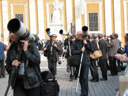 A troupe of photographers move to another viewpoint after the Pope made his way to the altar.
