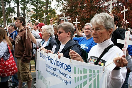 """Sisters Patty Fillenwarth, Stacy Pierce and Jacquelyn Hoffman approach the fence during the roll call. As names of those killed are read one by one, the crowd responds with """"Presente."""""""