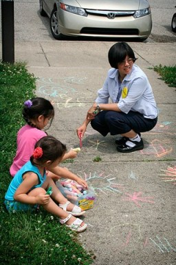 Sister Anna Ho helps young artists decorate the sidewalk outside of Providence Center.