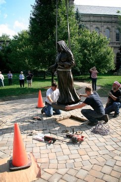 The workers make sure that Mother Theodore will fit in the space allotted for her.