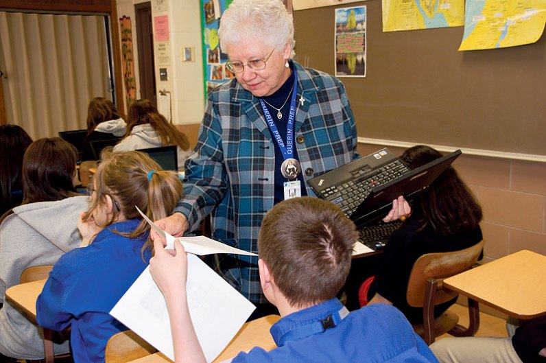 Sister Kay with her laptop in hand, assists a student in a theology class.