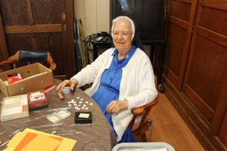 Sister Helen Dolores Losleben takes a break from her part in the creation of Saint Mother Theodore Guerin relic cards on July 17, 2012, in the Activity Room of Providence Hall.