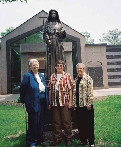 Standing with the Saint Mother Theodore Guerin statue at the Ft. Wayne, Ind., mausoleum dedicated to Mother Theodore Guerin are, from left, Sister Mary Ann Fox, Sister Jane Marie Osterholt (RIP), and Sister Donna Butler.