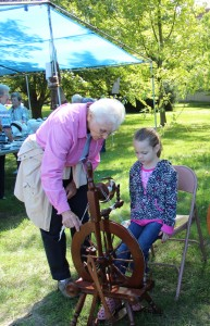 Sister Jeanne Knoerle gives a fiber spinning lesson to this young girl at a White Violet Farm Alpacas open house.