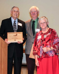 Earl Rodgers, left, and Keith Ruble, center, accept the Sarah and Joseph Thralls Award at the dinner.