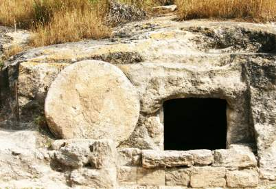 A first century ancient tomb with the stone rolled aside in Israel, similar to the type of resting place that Jesus would have been buried in.