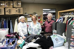 Faithful volunteers at The Helping Hands, from left, Milly Barbour, Bonnie Monaghan and Carol Robinson have fun together while sorting and hanging clothes.