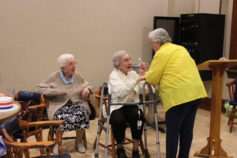 Sisters Marie Victoria Podesta and Mary Imelda Coulup greet Providence Associate Sheila Donis during Sunday's social.