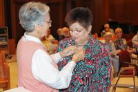 Sister of Providence Companion Sister Barbara Bluntzer pins the Providence Associate pin on Diana M. Garza during the ceremony Oct. 21 in Owens Hall Chapel.
