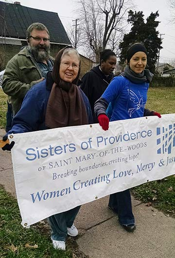 Sister Donna Butler and postulant Tracey Horan hold a Sisters of Providence of Saint Mary-of-the-Woods sign during the Unity March for Equality on Saturday, Dec. 13. The photo was taken by Sister Barbara Battista.