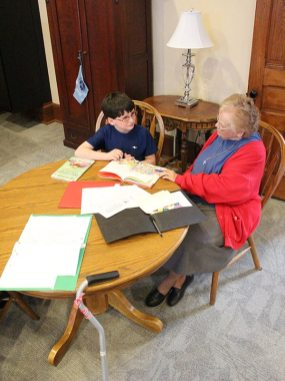 Sister Regina Norris helps a little boy with his reading in 2014 from the parlor in her home, Providence Hall.