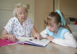 Sister Jean Arkenberg (RIP) helps a little girl with her reading in 2006.