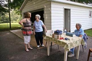 """From left: Current EFS Director Penny Sullivan, previous EFS Director Sister Margaret Quinlan and volunteer Sister Suzanne Buthod help out at a """"drive and dine"""" fundraiser for EFS."""
