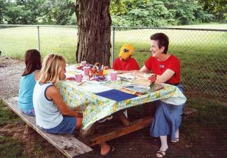 Mickie Lane Fredericks, assistant education coordinator, works with some students outside at Educational/Family Services in the summer of 2000.