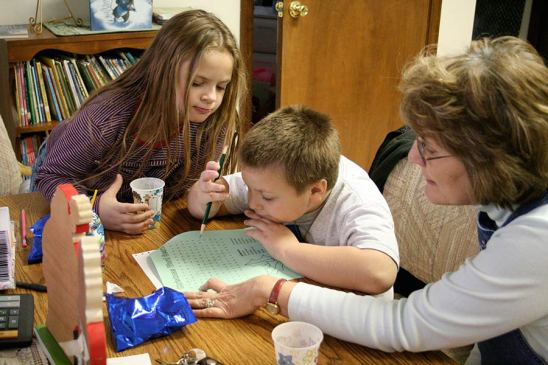 Randi Everett, then-administrative assistant at EFS, helps a student with his homework in 2008 while his sister looks on.