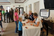 Sister Camille Neubauer and SP staff member Paula Sprigg greet visitors signing up for a shrine tour.