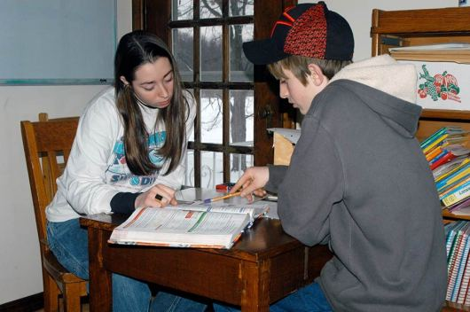 Saint Mary-of-the-Woods College student Tiffany Winhold helps a student with his math after school at EFS in 2010.