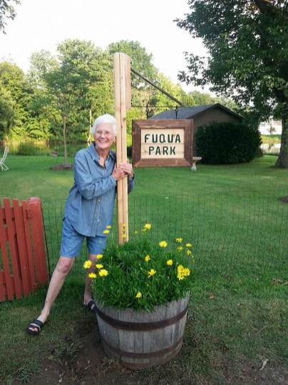 A more recent photo of Sister Jean Fuqua next to the sign marking the area surrounding the lake with its new name, Fuqua Park.