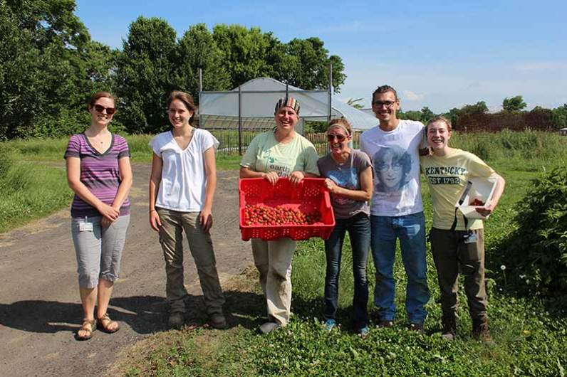 White Violet Center staff and volunteers show off their berry harvest
