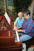 Sister Regina Marie McIntyre instructs Sister Joni Luna on the piano.