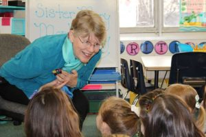 Sister Mary Montgomery explains the meaning behind a cross to students at St. Patrick School.